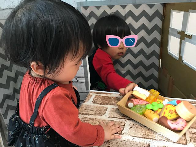 カフェ風ダンボールハウスで遊ぶ2人の子供の写真です。