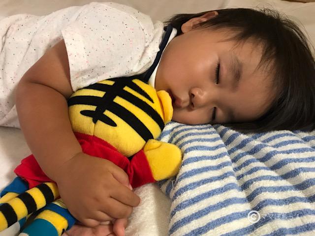しまじろうパペットと眠る子供の写真です。